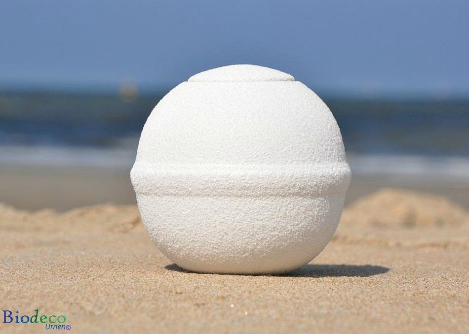 De witte Quartz Rond mini zee-urn op het strand met de Noordzee op de achtergrond