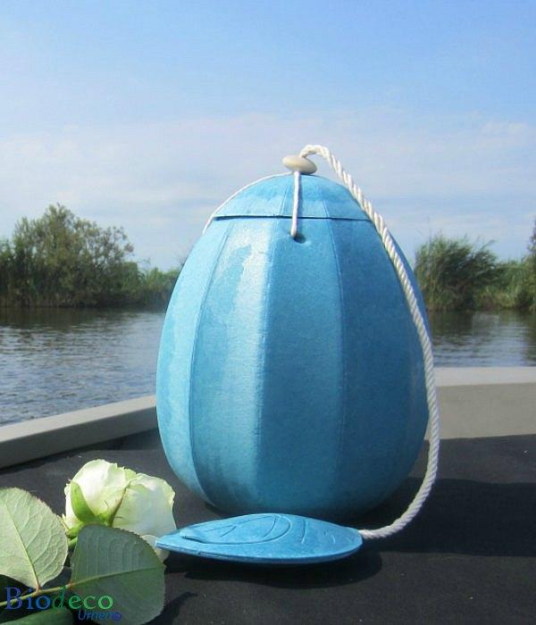 De zee-urn Beyond in het lichtblauw, opgesteld op het voordek van een boot, om in het water bij te zetten
