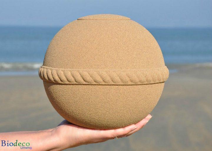 De Sand Round zee-urn in de hand, op het strand van Scheveningen