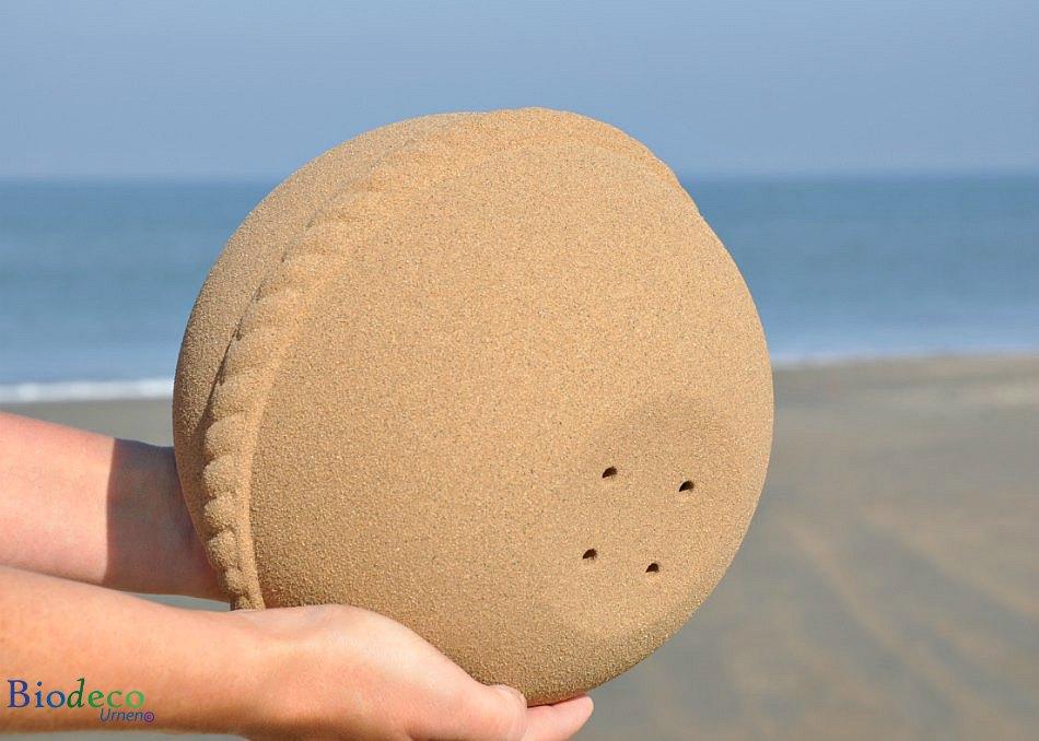 De onderkant van de Sand Round zee-urn met vier gaatjes, voor het verplaatsen van lucht in de urn tijdens een asbijzetting