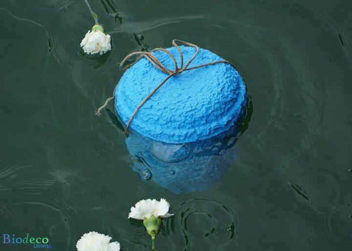 De zee-urn Zeeblauw, door middel van een touw bijgezet in de Noordzee voor de kust van IJmuiden, met bloemen als laatste groet