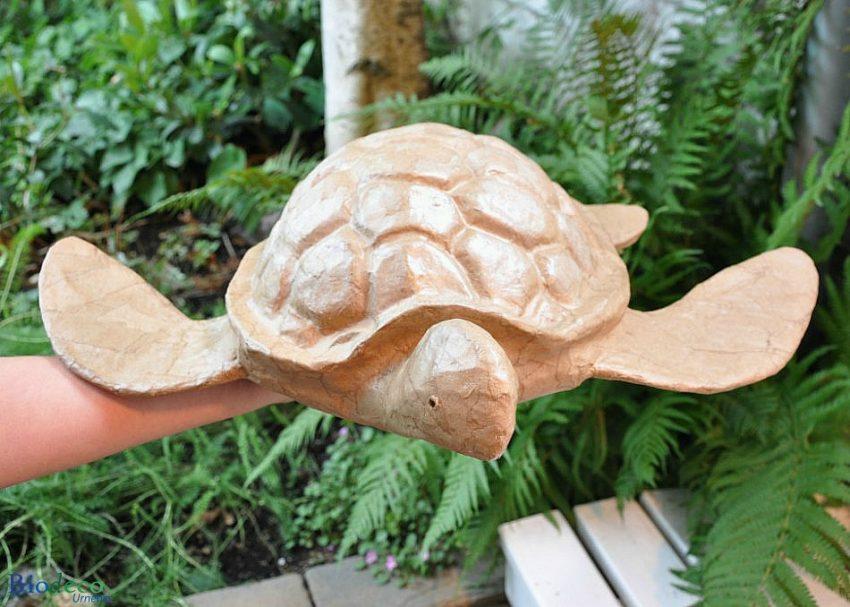 De mooie biologisch afbreekbare zee-urn Schildpad, gemaakt van gerecycled papier, op de hand gedragen