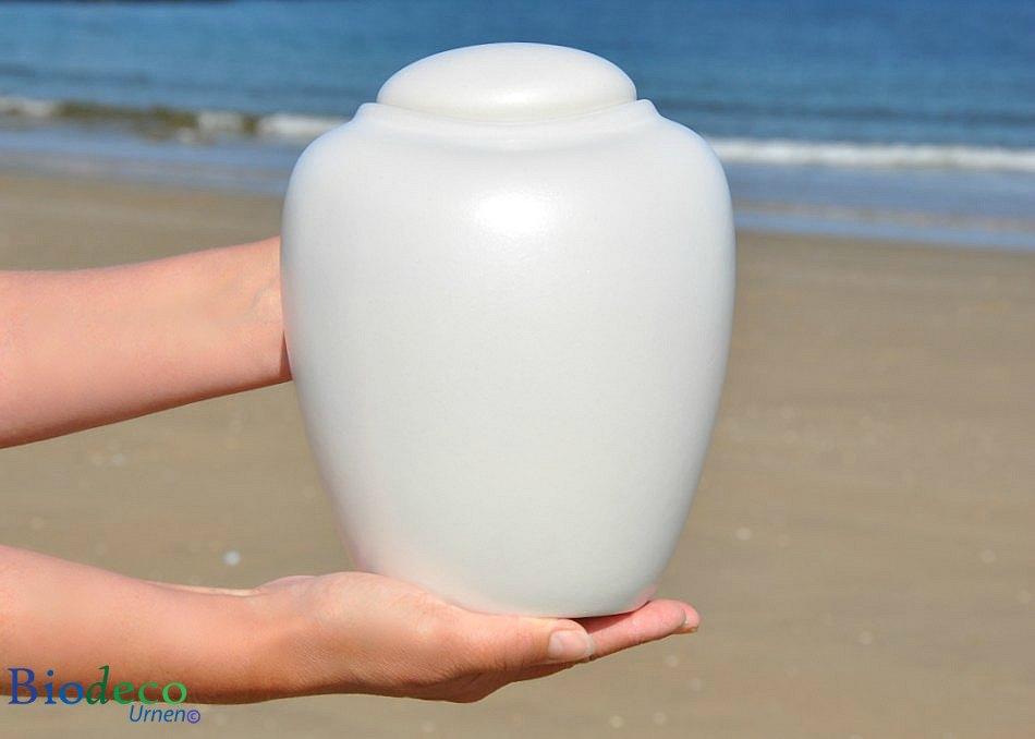 De zee-urn Ocean Parel, biologisch afbreekbare urn in handen gedragen op het strand van Scheveningen