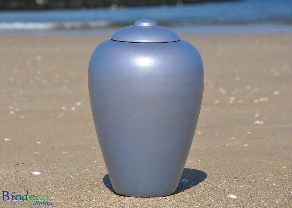De biologisch afbreekbare zee-urn Classic Aqua, op het strand van Scheveningen voor de branding van de Noordzee