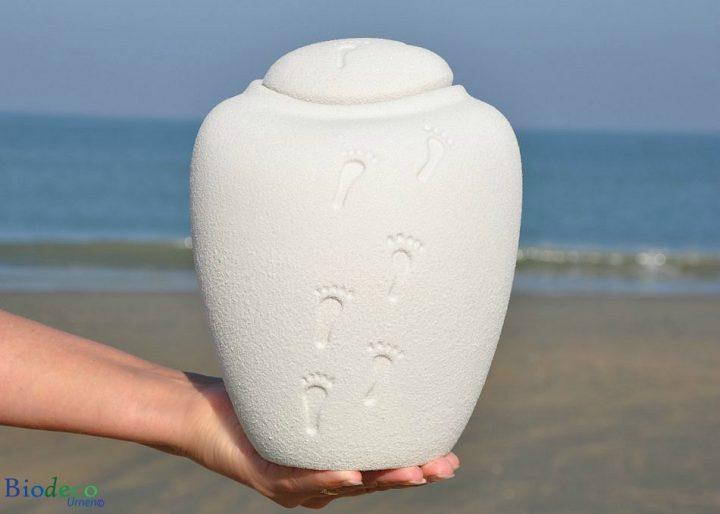 De biologisch afbreekbare zee-urn Ocean Ouartz Footprints op handen gedragen, voor de branding van de Noordzee bij Scheveningen