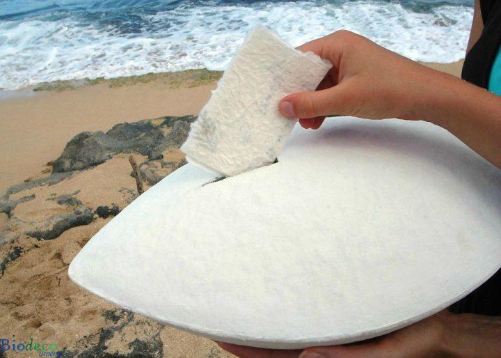 De biologisch afbreekbare zee-urn Memento wit, in handen gedragen op het strand, voor een asbijzetting op zee